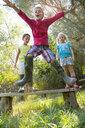 Boy jumping off garden seat - CUF35260
