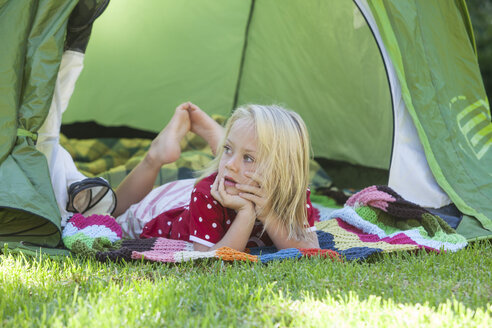 Portrait of girl daydreaming in garden tent - CUF35275