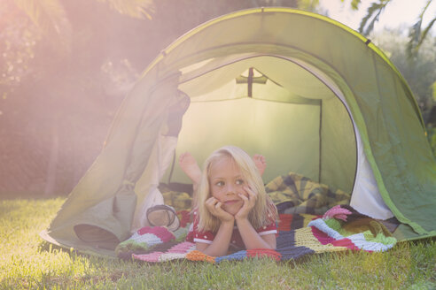 Portrait of girl lying gazing from garden tent - CUF35278