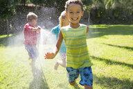 Three children chasing each other in garden with water sprinkler - CUF35281