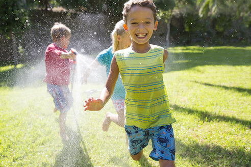 Three children chasing each other in garden with water sprinkler - CUF35281