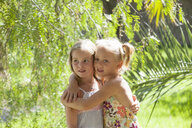 Candid portrait of two girls with arms around each other in garden - CUF35320