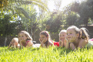 Five girls lying in a row in garden with chins on hands - CUF35326