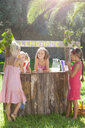 Four girls buying and selling at lemonade stand in park - CUF35329