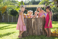 Five girls pouring lemonade and chatting at lemonade stand in park - CUF35332