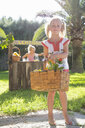 Portrait of girl carrying basket of lemons in front of  lemonade stand - CUF35335