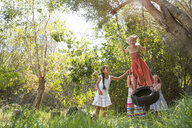 Four girls playing on tree tire swing in garden - CUF35341