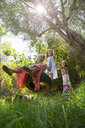 Low angle view of three girls playing on tree tire swing in garden - CUF35344