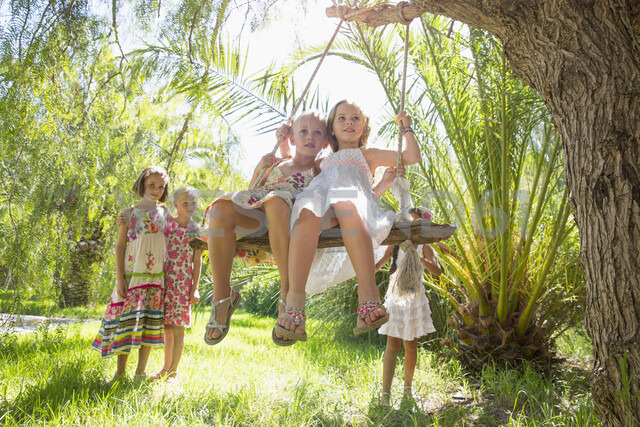 Five girls playing with tree swing in garden - CUF35347