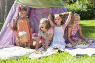 Five girls playing in garden teepee - CUF35350