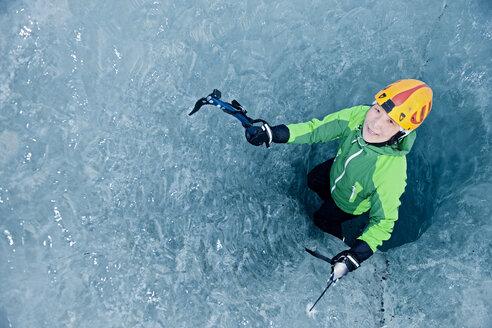 Female ice climber climbing out of pothole in glacier, Svinafellsjokull, Vatnajokull National Park, Iceland - CUF35401