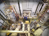 Engineers in seawater pumping station of power station, high angle view - CUF35416
