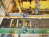 Workers in turbine hall of power station, high angle view - CUF35431