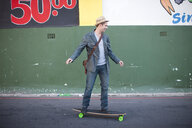 Mid adult male skateboarding on city street - CUF35449