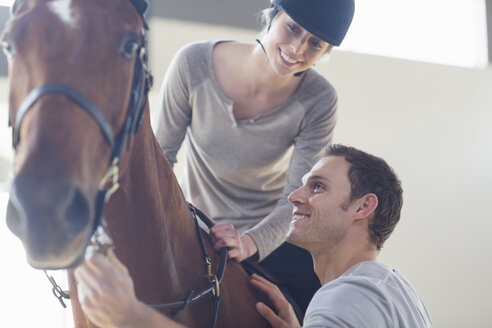 Young female horseback rider with instructor in indoor paddock - CUF35752