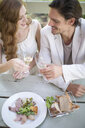 Couple toasting with champagne at table in garden restaurant - CUF35764