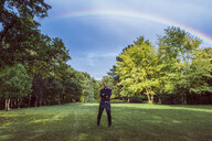 Young businessman standing in park under a rainbow, with arms crossed - JSCF00103