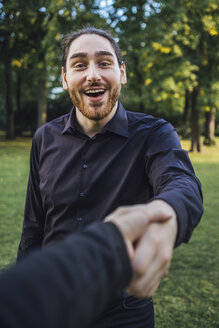 Young businessman greeting business partner in a park, negotiating business transactions - JSCF00106
