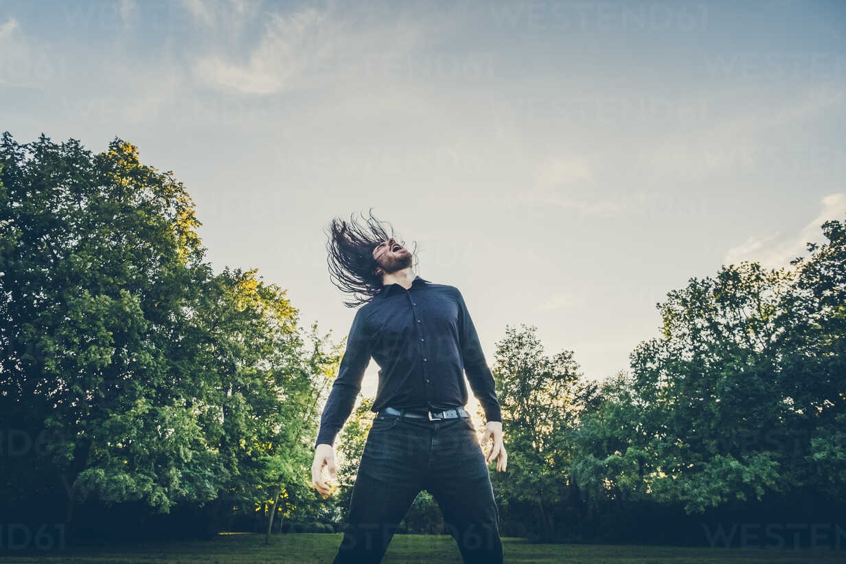 Heavy metal fan headbanging in a park - JSCF00121 - Jonathan Schöps/Westend61