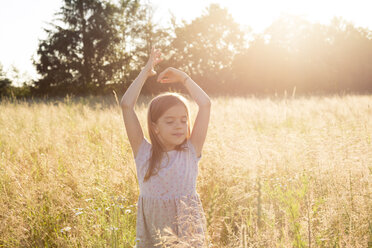 Young girl standing in field at summer evening - LVF07160