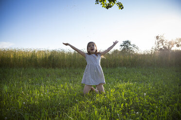 Young girl kneeling on meadow at summer evening - LVF07163
