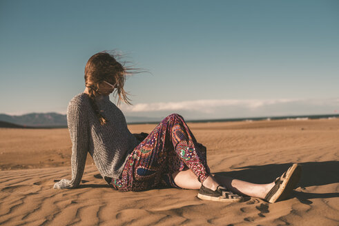 Spain, fashinable young woman sitting on the beach - ACPF00054
