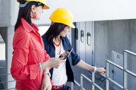 Businesswomen in safety helmet at balcony - CUF36048