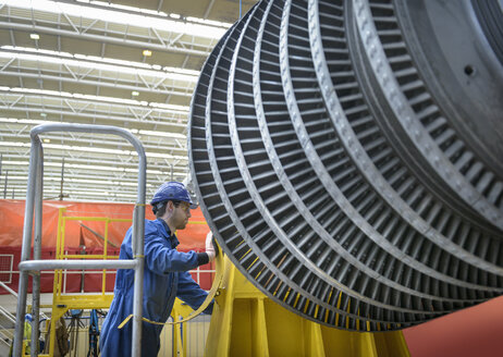 Engineer inspecting turbine during power station outage - CUF36078