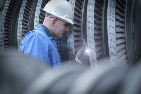 Engineer with torch inspecting turbine during power station outage - CUF36081