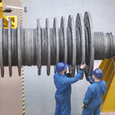 Engineers inspecting turbine  during power station outage, high angle view - CUF36096