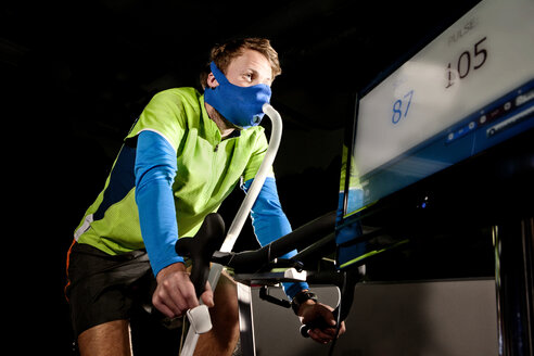 Young man in face mask on gym exercise cycle in altitude centre - CUF36219