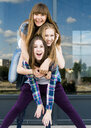 Three young women stacked on top of each other in city - CUF36270