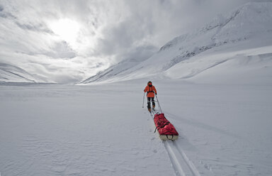Female touring skier pulling an expedition sled in snow, Oxnadalsheidi, North Iceland, Iceland - CUF36303