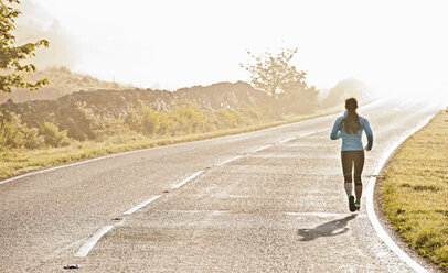 Rear view of female runner running on misty road, Capel Curig, Snowdonia, North Wales, UK - CUF36306