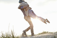 Young couple hugging on Bournemouth beach, Dorset, UK - CUF36345