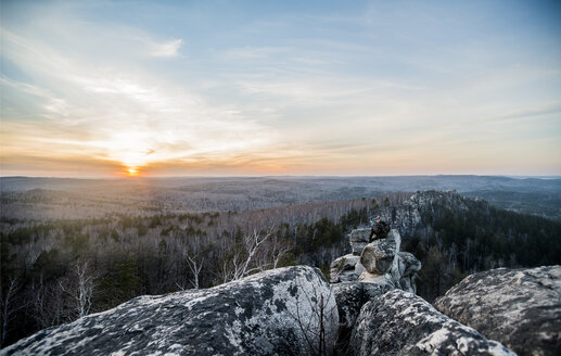 Young male hiker on top of rock formation at sunset - CUF36369