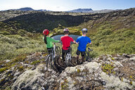 Cyclists looking out into a craterlake, Nesjavellir, Thingvellir national park, Iceland - CUF36432