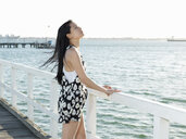 Young woman gazing from pier, Port Melbourne, Melbourne, Victoria, Australia - CUF36516