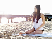 Young woman drinking coffee on beach, Port Melbourne, Melbourne, Victoria, Australia - CUF36519