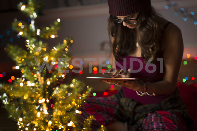 Young woman using digital tablet and preparing for christmas - ISF14443 - Steve Prezant/Westend61
