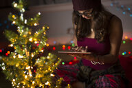 Young woman using digital tablet and preparing for christmas - ISF14443