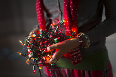 Close up of young woman holding tangle of christmas lights - ISF14449