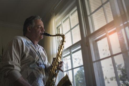Mature man at home playing saxophone - ISF14491
