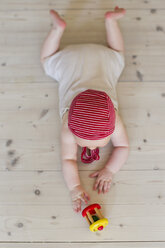 Baby girl lying on floor with toy - CUF36779