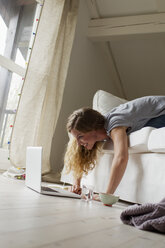 Woman lying on sofa using laptop - CUF36869