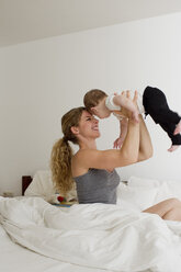 Mother holding baby boy up in mid air - CUF36881