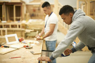 Two male college students in woodworking workshop - CUF36896
