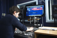 Male student using sound mixing equipment in college music booth - CUF36899