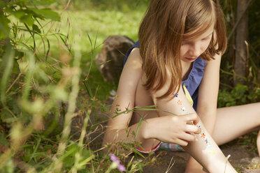 Girl sticking stars on legs in garden - CUF36905