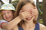 Girl with hands over her sisters eyes in garden - CUF36911